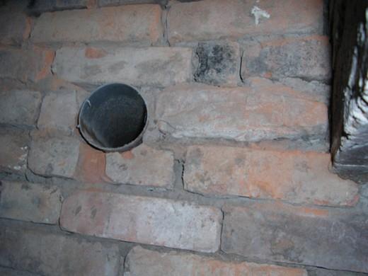 На фото: вентиляционное отверстие в кирпичном погребе сарая