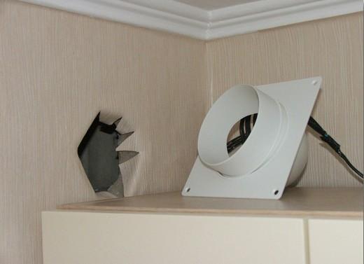 На фото - процесс монтажа обратного клапана для вентиляции на кухне
